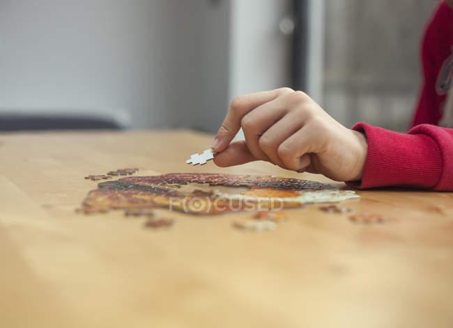 Рука мальчика, размещение кусок головоломки на головоломки столом — стоковое фото