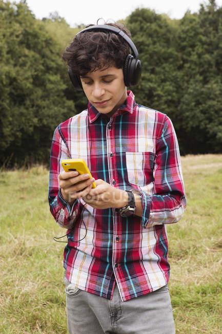 Adolescent, restant dans des champs, utilisant des écouteurs, utilisant le smartphone — Photo de stock