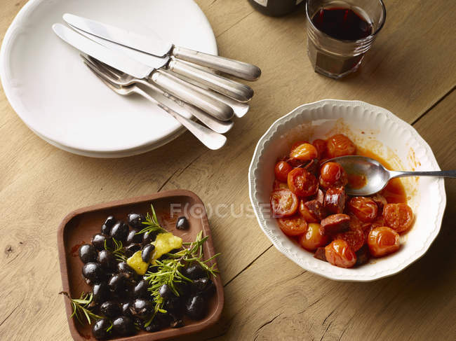 Top view of table with bowl of black olives and bowl of tomatoes — Stock Photo