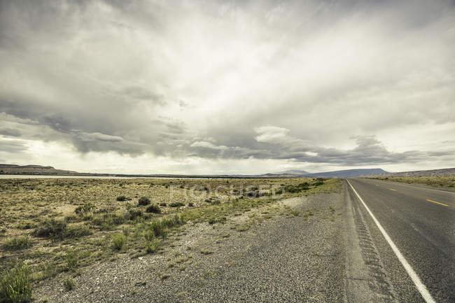 Route de vide dans le paysage distant, Cody, Wyoming, Usa — Photo de stock