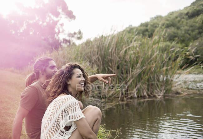 Пара, сидя у реки ищет прочь улыбаясь, указывая — стоковое фото