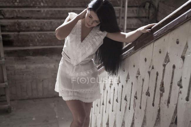 Giovane donna in piedi contro ringhiera di scala — Foto stock