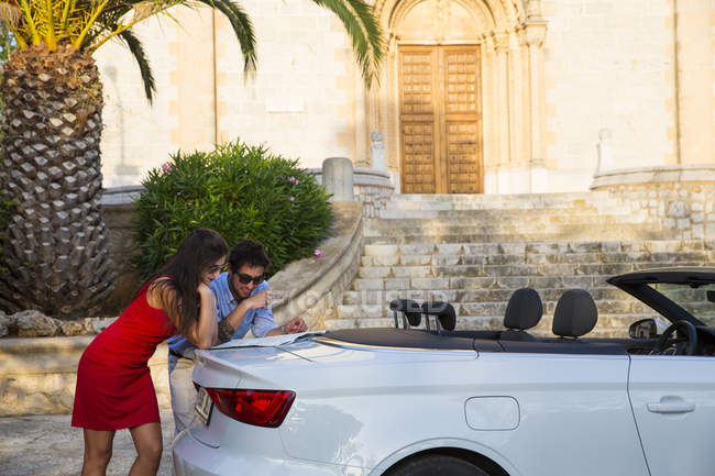 Coppia giovane appoggiata alla decappottabile guardando la mappa, Calvia, Maiorca, Spagna — Foto stock
