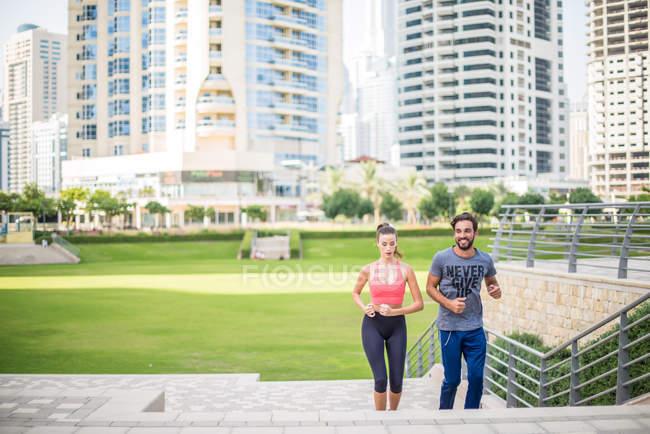 Courir en couple, monter l'escalier du parc, Dubaï, Émirats arabes unis — Photo de stock
