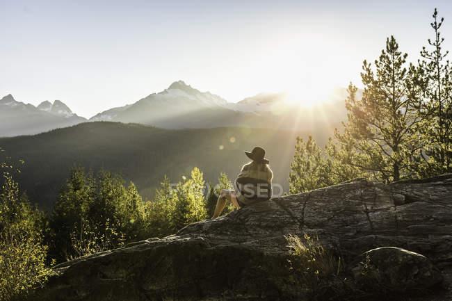 Жінка, сидячи на скелі, дивлячись на вигляд, заднього виду — стокове фото