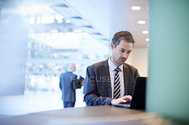 Бізнесмен набравши на ноутбуці в офісі, люди у фоновому режимі — стокове фото