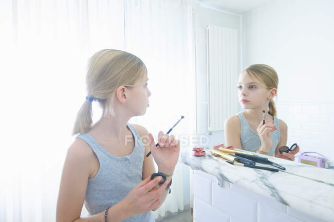 Bedroom mirror image of girl with make up brush staring at ...
