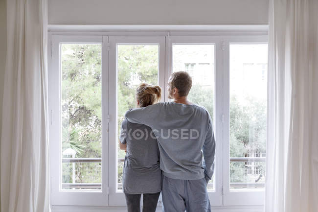 Mid adult couple at home, looking out of window, man hugging woman, rear view — Stock Photo