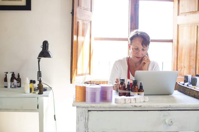 Mulher falando no smartphone enquanto usa laptop no escritório de oficina de sabão artesanal — Fotografia de Stock