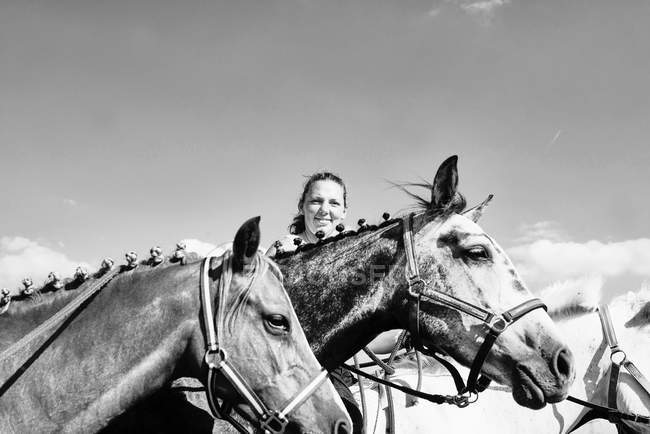 B & W image of woman with horses — Stock Photo