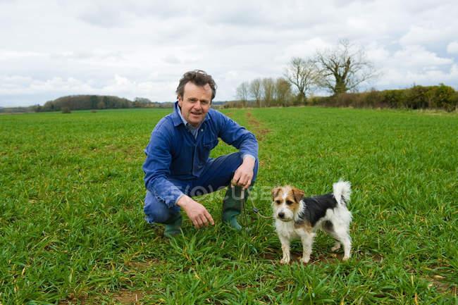 Ritratto di agricoltore accovacciato in campo con cane — Foto stock