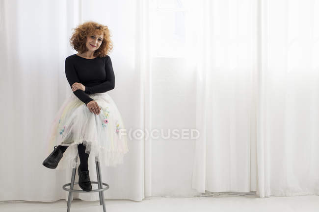 Portrait of woman sitting on stool looking at camera — Stock Photo