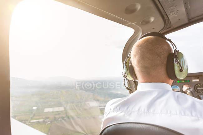 Vista posterior de piloto en cabina de avión, en vuelo - foto de stock