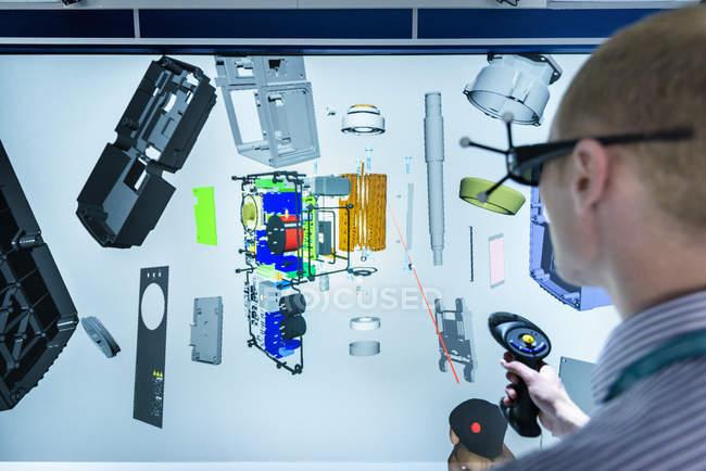 Інженер дивлячись на складові частини машини в 3D у віртуальній реальності Suite — стокове фото