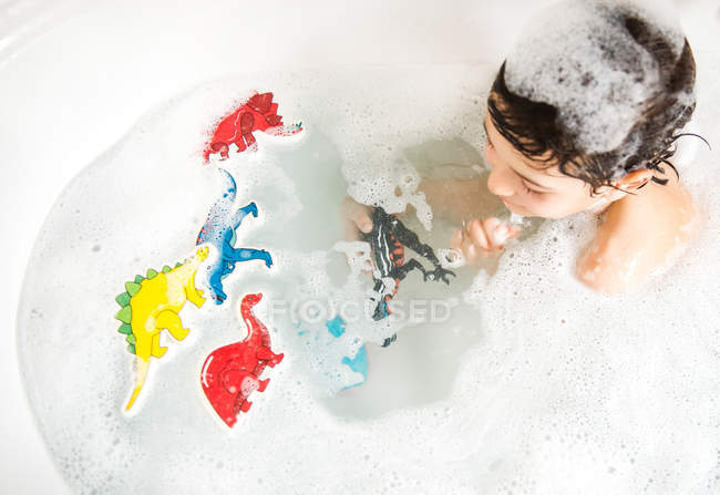 Boy playing with toys in bath, elevated view — Stock Photo