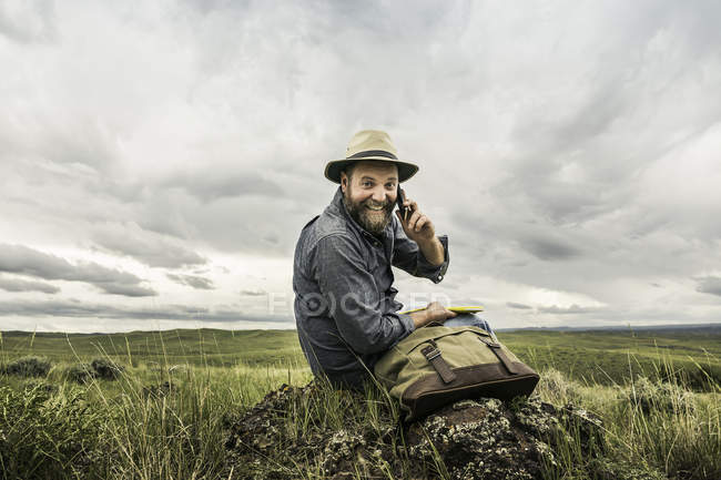 Portrait of mature male hiker sitting on rocks using smartphone, Cody, Wyoming, USA — Stock Photo