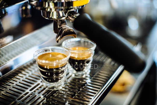 Two shot glasses of espresso on espresso machine — Stock Photo