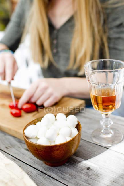 Обрезанное изображение женщины, рубящей помидоры напитком в стекле на переднем плане — стоковое фото