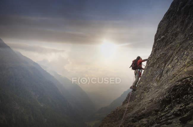 Escalador em uma parede rochosa acima de um vale, Alpes, Cantão Berna, Suíça — Fotografia de Stock