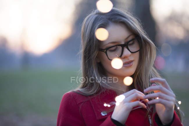 Молодая женщина в парке, глядя на огни в руке, Лондон, Великобритания — стоковое фото