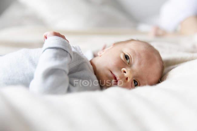 Baby boy lying on blanket looking away — Stock Photo