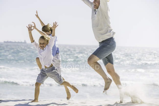 Father and children jumping on beach — Stock Photo