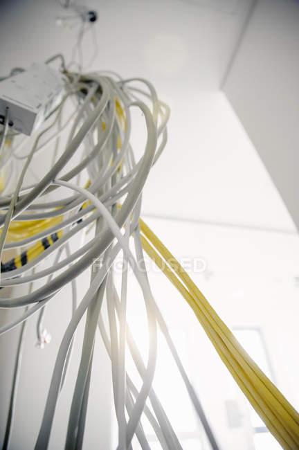 Vista de ángulo bajo con variedad de cables de red y de alimentación que cuelgan del nuevo techo de oficina - foto de stock