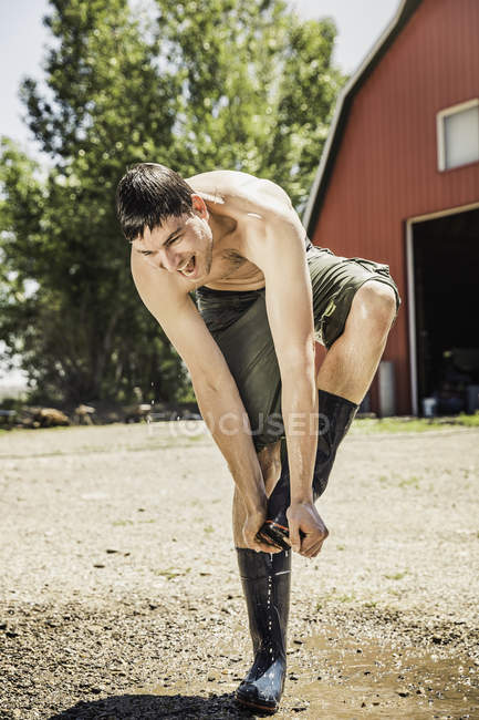 Wet farmworker removing rubber boots smiling — Stock Photo