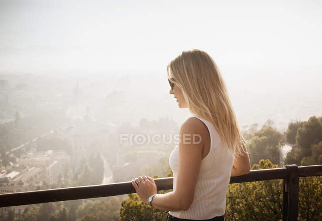 Woman on balcony looking at elevated view of Malaga, Spain — Stock Photo