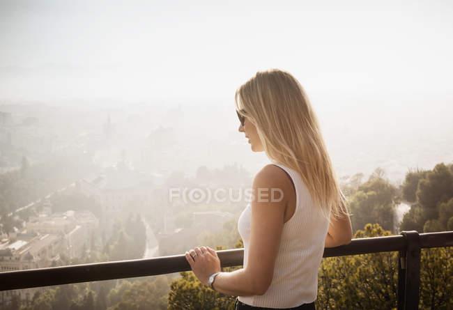 Donna sul balcone guardando vista elevata di Malaga, Spagna — Foto stock