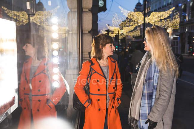 Deux amis féminins ayant la conversation à l'extérieur du magasin — Photo de stock