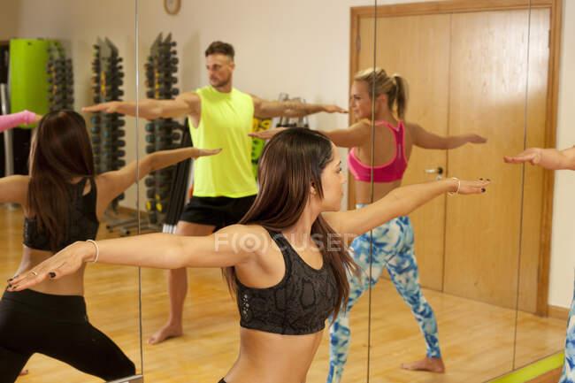 Spiegelbild von Menschen im Fitnessstudio, Arme weit gestreckt — Stockfoto