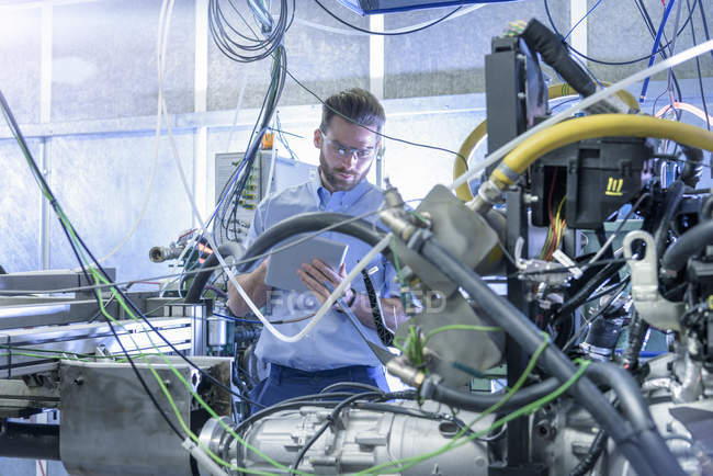 Engineer with car engine in testing bay of automotive parts factory — Stock Photo