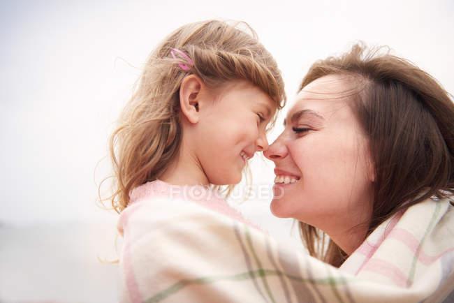 Mère et fille heureuses enveloppées dans une couverture, le nez frottant — Photo de stock