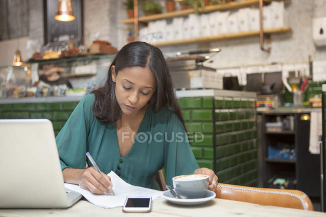 Mid adult woman doing paperwork at cafe table — Stock Photo