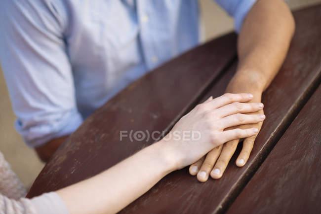 Ausgeschnittene Ansicht eines Paares, das sich am Tisch an den Händen hält — Stockfoto