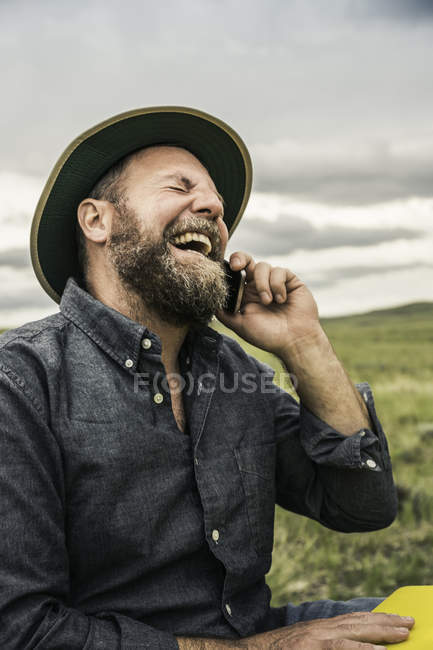Male hiker laughing whilst using smartphone, Cody, Wyoming, USA — Stock Photo