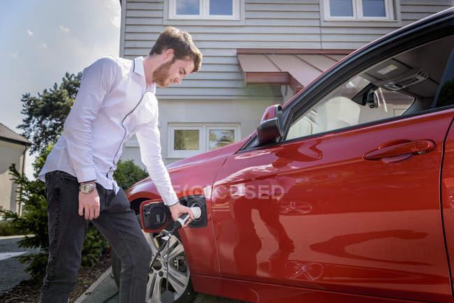 Людина зарядки електричний автомобіль — стокове фото