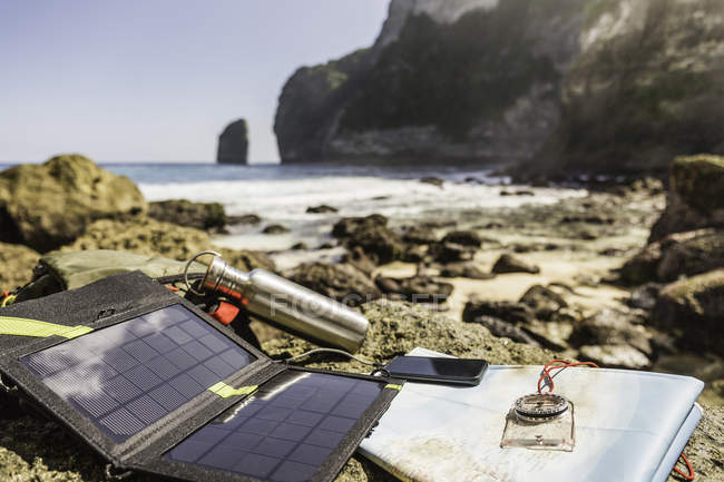 Solar battery charger and smartphone on beach, South Coast, Nusa Penida, Indonesia — Stock Photo