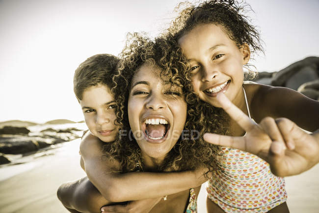 Happy mother and children showing peace sign on beach — Stock Photo