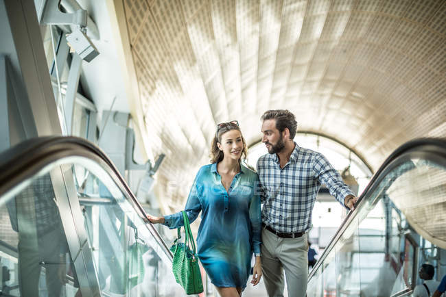 Couple de touristes remontant escalator shopping mall, Dubai, United Arab Emirates — Photo de stock