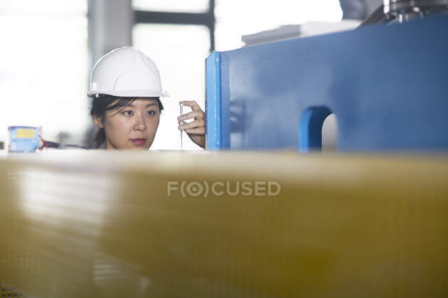 Technician checking readings on gauge in factory — Stock Photo