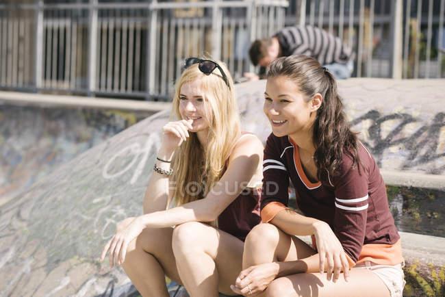 Two female skateboarders sitting in skatepark — Stock Photo