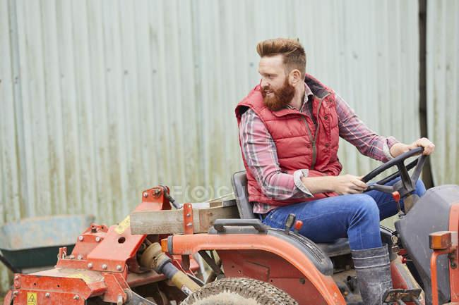 Mann fährt Traktor auf Bauernhof — Stockfoto
