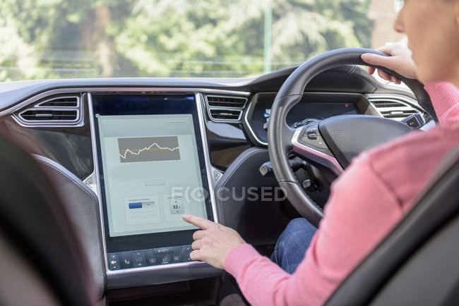 Жінка, використовуючи графічний дисплей в електричний автомобіль — стокове фото