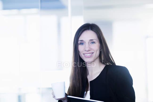 Jovem segurando xícara de café e arquivo de pasta de anel olhando para a câmera sorrindo — Fotografia de Stock