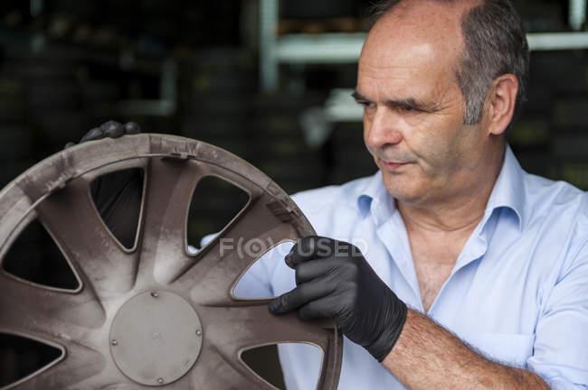Mechanic examining wheel hub in repair garage — Stock Photo