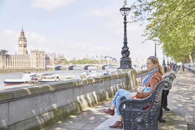 Mother and son resting on bench by river thames, London, UK — стокове фото
