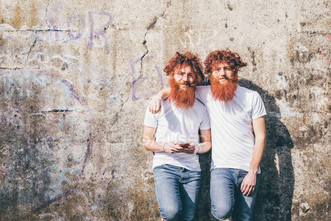 Portrait of young male hipster twins with red beards standing in front of wall — Stock Photo
