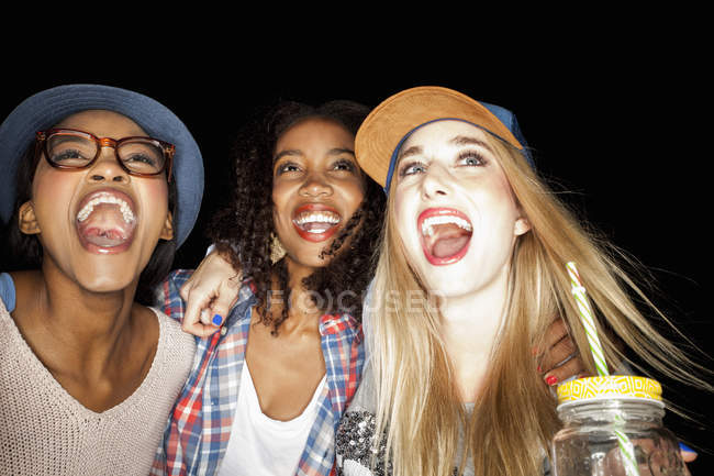 Les jeunes femmes blotties ensemble regardant vers le haut, les bouches ouvertes souriant — Photo de stock